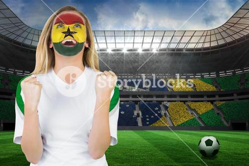 Excited ghana fan in face paint cheering