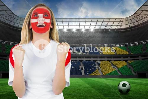 Excited fan in swiss face paint cheering