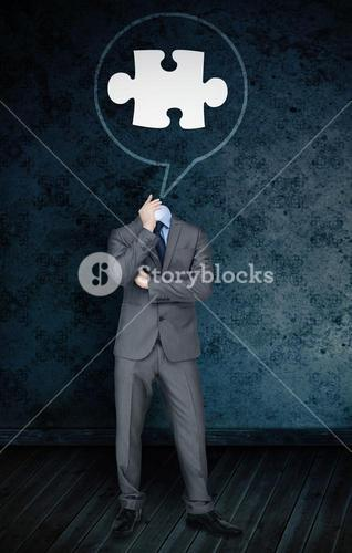 Composite image of headless businessman with jigsaw in speech bubble