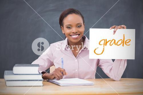 Happy teacher holding page showing grade