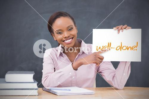 Happy teacher holding page showing well done