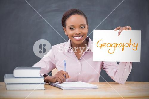 Happy teacher holding page showing geography