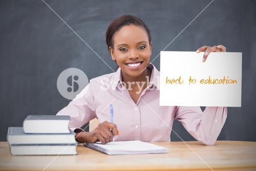 Happy teacher holding page showing back to education
