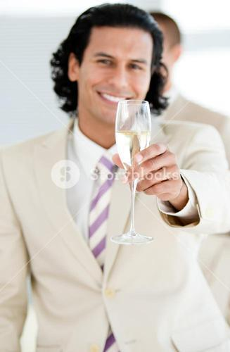 Cheerful businessman holding a glass of Champagne