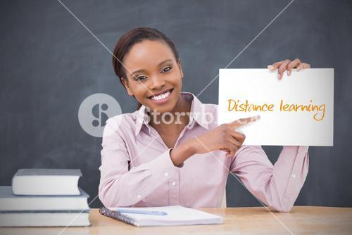 Happy teacher holding page showing distance learning