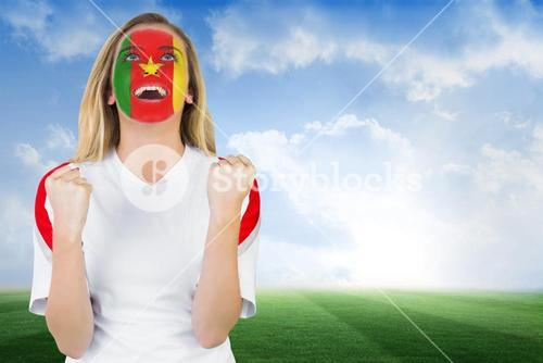 Excited cameroon fan in face paint cheering