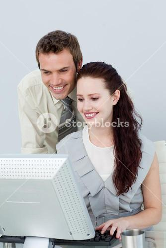 Attractive business people using a computer