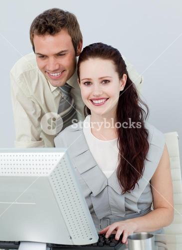 Beautiful businesswoman and attractive businessman using a computer