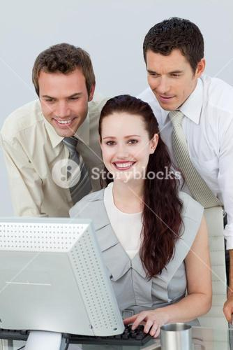 Three young business people using a computer