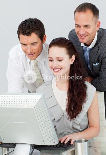 Three business people using a computer