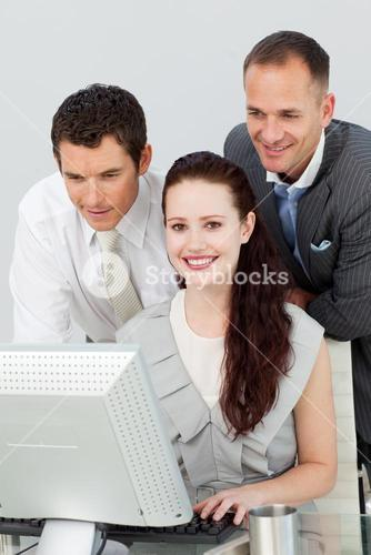 Smiling businesswoman and two businessmen using a computer