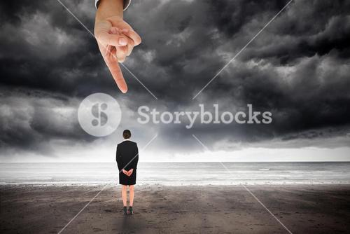 Giant hand pointing at young businesswoman standing with hands behind back