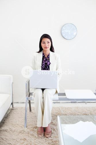 Woman working on a laptop in a wiating room