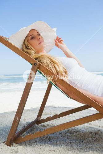 Gorgeous blonde sitting at the beach wearing sunhat