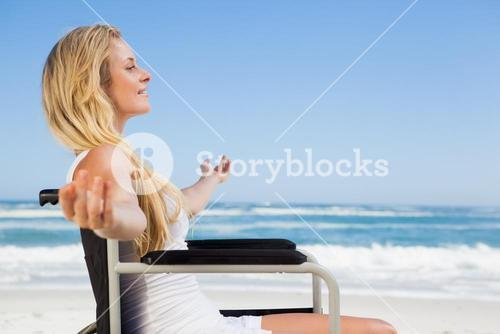 Wheelchair bound blonde smiling on the beach