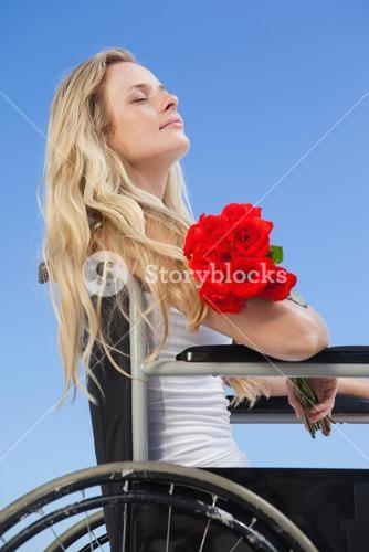 Wheelchair bound blonde smiling on the beach holding roses