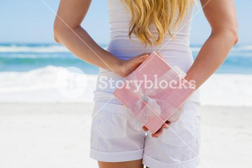 Blonde hiding present behind back on the beach