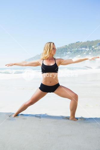 Fit blonde in warrior pose on the beach