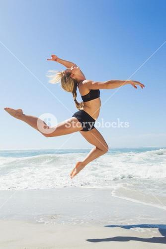 Fit blonde jumping gracefully on the beach