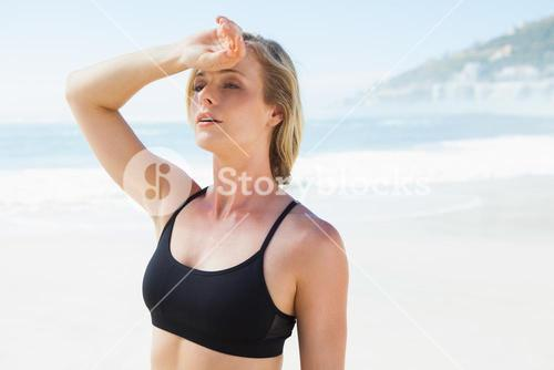 Fit blonde wiping her forehead on the beach