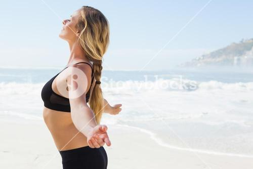 Fit blonde standing on the beach with arms outstretched