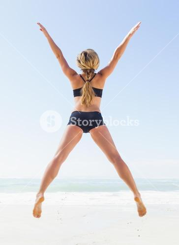 Fit blonde jumping on the beach with arms outstretched