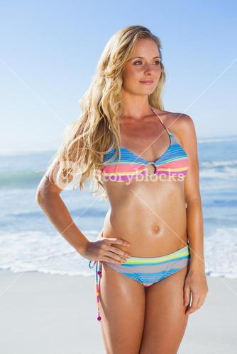 Gorgeous blonde in bikini on the beach smiling at camera