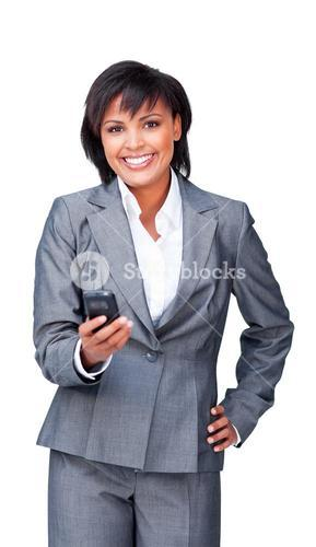 Attractive businesswoman smiling at the camera while sending a text