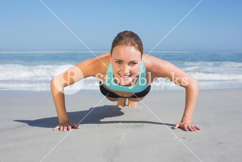 Fit woman in plank position on the beach