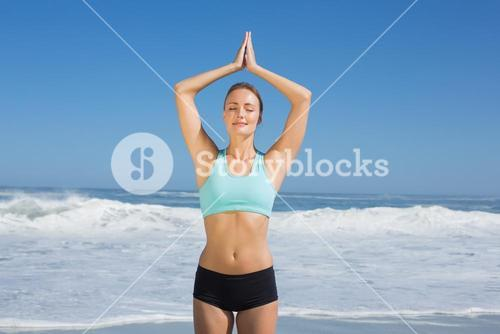 Fit woman standing on the beach with hands together