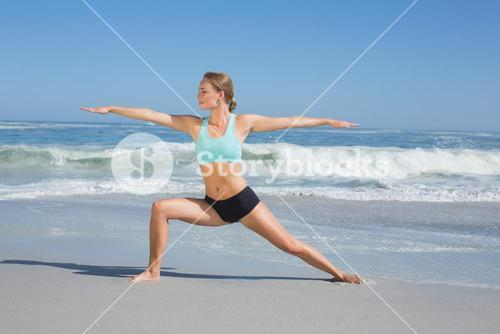 Fit woman standing on the beach in warrior pose