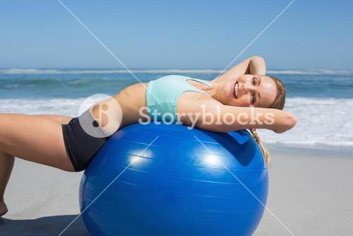 Fit woman lying on exercise ball at the beach stretching