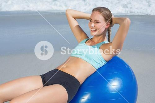 Fit woman lying on exercise ball at the beach doing sit ups