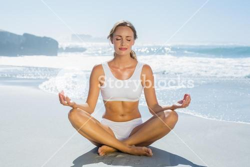 Gorgeous blonde in lotus pose by the sea