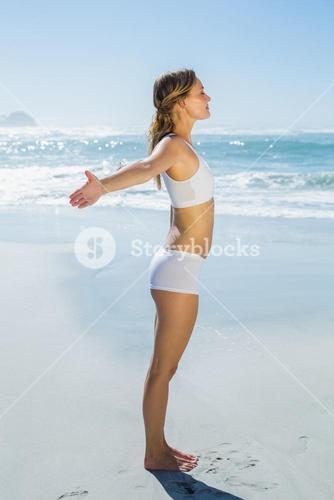 Gorgeous blonde standing with arms out by the sea