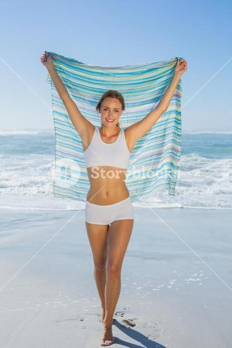 Gorgeous fit blonde standing by the sea with scarf