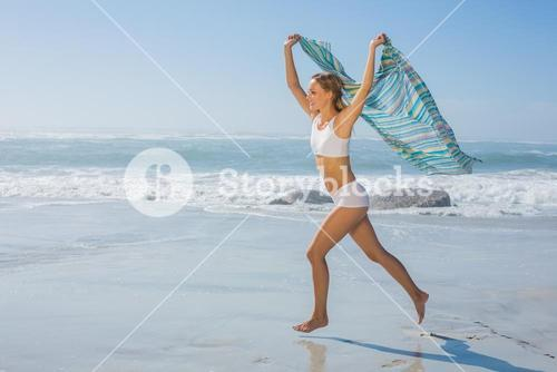 Gorgeous fit blonde running by the sea with scarf