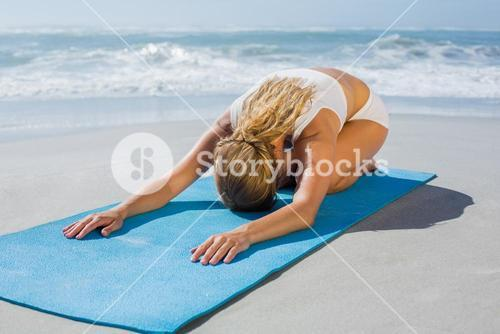 Gorgeous fit blonde in childs pose on the beach