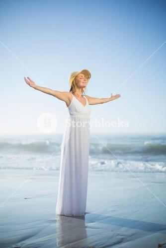 Smiling blonde standing on the beach in white sundress and sunhat