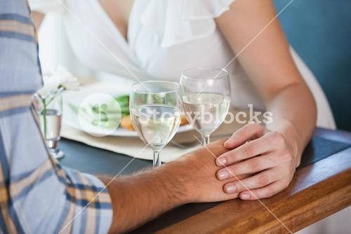 Couple holding hands at dinner