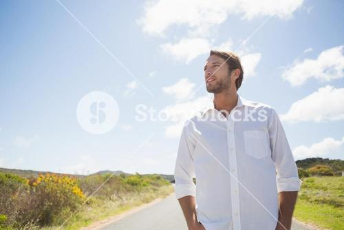 Handsome casual man standing on a road