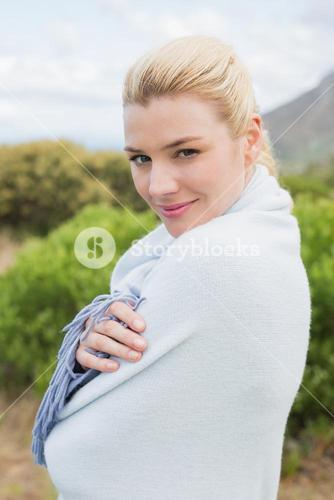 Pretty blonde wrapped up in blanket outside