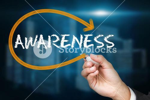 Businessman writing the word awareness