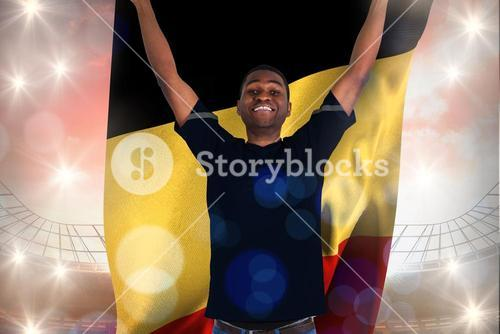 Composite image of excited football fan in black cheering holding belgium flag