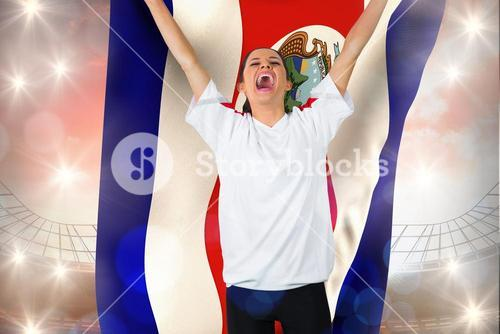 Composite image of football fan in white cheering holding costa rica flag