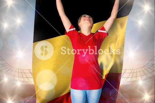 Composite image of cheering football fan in red holding belgium flag