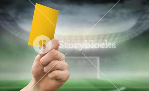 Composite image of hand holding up yellow card