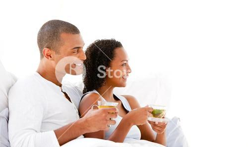 Cheerful couple drinking a cup of tea lying on their bed
