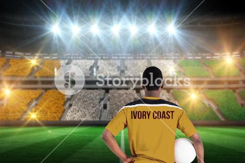 Composite image of ivory coast football player holding ball