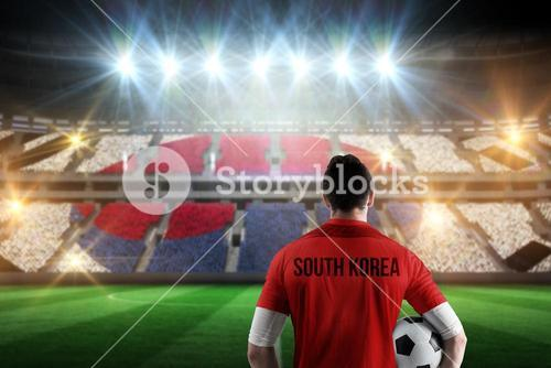 Composite image of south korea football player holding ball
